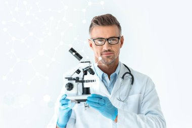 handsome scientist in glasses holding microscope and looking at camera isolated on white with technology interface