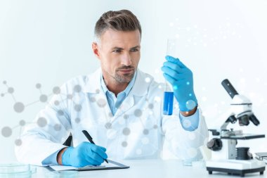 handsome scientist looking at test tube with blue reagent