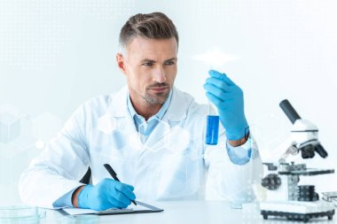 Handsome scientist looking at test tube with blue reagent stock vector