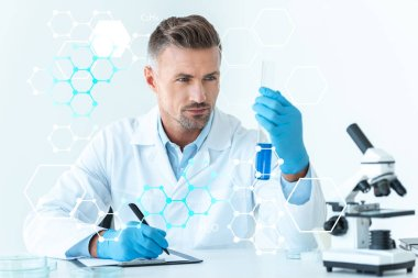handsome scientist looking at test tube with blue reagent isolated on white with medical symbols