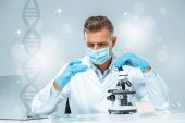 Photo handsome scientist in medical mask and medical gloves making experiment with dna