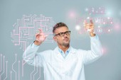 Fotografie handsome scientist in white coat and glasses moving brain interface with the future is now lettering isolated on white, artificial intelligence concept