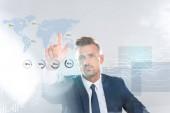 Fotografie pohledný podnikatel dotýká podnikání ikony prstem izolované na bílém, koncept umělé inteligence