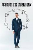 Fotografie pohledný podnikatel v modrém obleku stál a díval se na hostující izolované na bílém s ikonami financí a čas jsou peníze nápisy