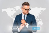 pohledný podnikatel nosí hodinky a pryč izolované na grey s světové mapy a hledání bar