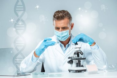 handsome scientist in medical mask and medical gloves making experiment with dna