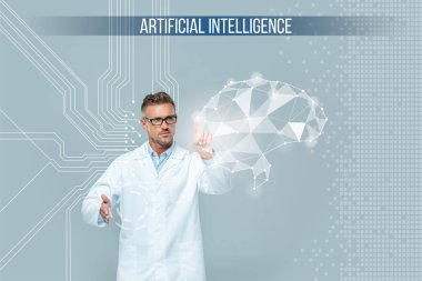 handsome scientist in glasses touching brain interface isolated on grey, artificial intelligence concept