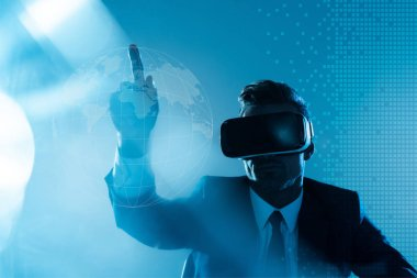 businessman in virtual reality headset pointing on globe isolated on blue, artificial intelligence concept