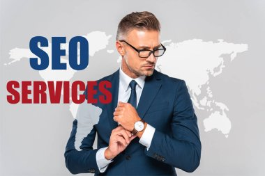 Handsome businessman wearing wristwatch and looking away isolated on grey with world map and seo services stock vector