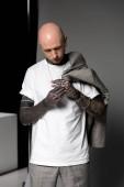 uomo calvo tatuato con giacca sulla spalla guardando le mani con i tatuaggi in studio