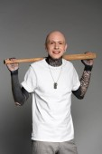 Photo cheerful tattooed man standing with baseball bat on shoulders and smiling at camera on grey