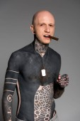 Fotografie confident bare-chested man with tattoos smoking cigar and looking at camera isolated on grey
