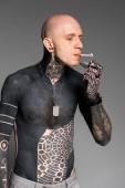 Fotografie plešatý shirtless Tetovaný muž osvětlení Cigaretový zapalovač izolované na šedou