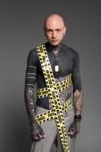 Fotografia uomo a torso nudo con tatuaggi e polizia linea intorno al corpo che guarda lobbiettivo isolata su grey