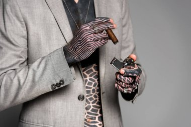 mid section of tattooed man in suit jacket holding cigar and lighter isolated on grey