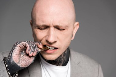 close-up view of bald tattooed man biting bitcoin isolated on grey