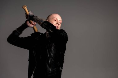 Aggressive bald tattooed man in leather jacket hitting with baseball bat isolated on grey stock vector