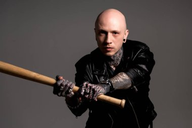 Aggressive bald tattooed man in leather jacket holding baseball bat and looking at camera isolated on grey stock vector