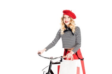 pretty woman in red beret holding shopping bags near bicycle isolated on white
