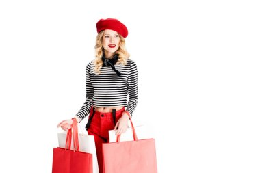 smiling woman standing with shopping bags isolated on white