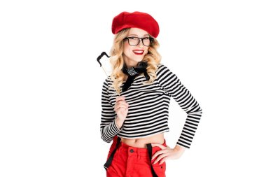 cheerful blonde woman in glasses holding fake mustache on stick isolated on white