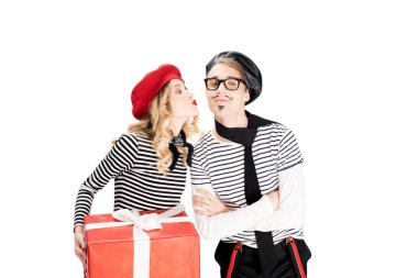 french man standing with crossed arms while attractive woman holding gift box and kissing cheek isolated on white
