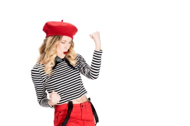 excited woman in red beret smiling while celebrating winning isolated on white