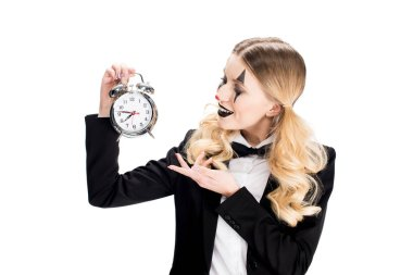 cheerful female clown looking at alarm clock isolated on white