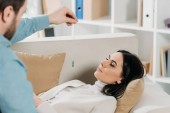 Fotografie zugeschnittenen Schuss von bärtigen Hypnotiseur hypnotisierenden junge Frau mit geschlossenen Augen auf couch