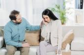 vousatý psychoterapeut podporující mladá rozrušená žena pláče na gauči