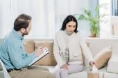 Fotografie naštvaná mladá žena držící kosmetický ubrousek během sezení s psychiatrem