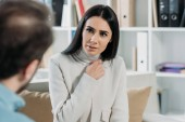 selective focus of unhappy young patient looking at psychiatrist in office