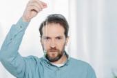 Fotografie ernsthafte bärtigen männlichen Hypnotiseur, pendeln und Blick in die Kamera halten