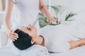 Photo cropped shot of peaceful young woman receiving reiki healing treatment on head and chest