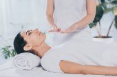 Photo cropped shot of peaceful young woman with closed eyes receiving reiki healing treatment