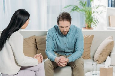 young psychotherapist talking with upset bearded man sitting on couch