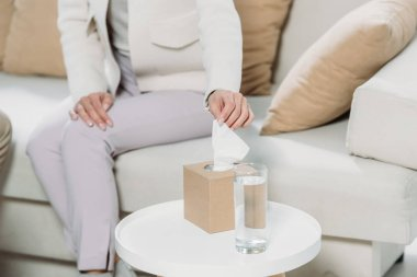 cropped shot of woman sitting on couch and holding paper tissue in psychotherapist office