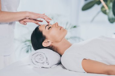 cropped shot of reiki specialist doing healing therapy to calm young woman with closed eyes