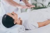 mladá žena leží na lehátku a léčby reiki