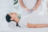 Photo cropped shot of young woman with closed eyes receiving reiki treatment