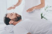 cropped shot of healer doing reiki healing session to calm bearded man with closed eyes