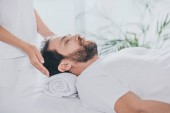 cropped shot of man with closed eyes receiving reiki treatment