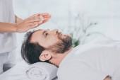 Photo partial view of calm bearded receiving reiki treatment and looking up