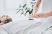 Photo cropped shot of bearded man lying and receiving reiki treatment on stomach