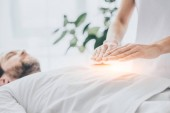 Photo cropped shot of man receiving reiki treatment on stomach