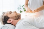 Photo cropped shot of bearded man looking up while receiving reiki treatment