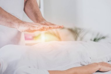 Cropped shot of male healer doing reiki treatment session to woman stock vector