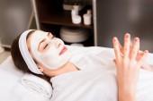 Frau liegt im weißen Bademantel mit aufgesetzter Gesichtsmaske im Schönheitssalon