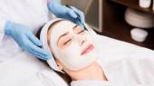 Kosmetikerin stehen in der Nähe von Frau mit kosmetischen Maske auf Gesicht und hält Kosmetik Pinsel im Schönheitssalon