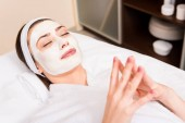 nő feküdt fehér fürdőköpeny és hairband, az alkalmazott arcpakolás szépségszalon: